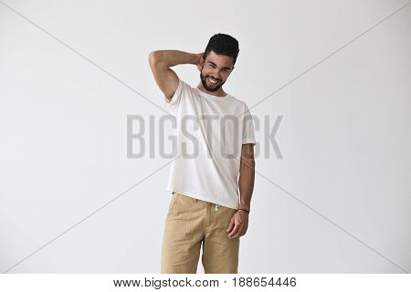 Frontal shot of attractive young hispanic man who chuckles and smiles into camera in fashion pose in white blank simple tshirt from premium materials cotton and vyscose