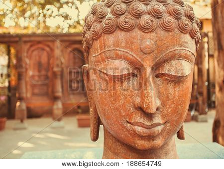 Buddha statue face with closed eyes in calm area of asian town with temples.