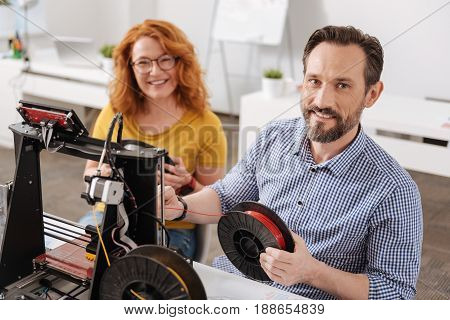 Pleasurable work. Joyful happy nice designer looking at you and smiling while having a 3d filament in his hands