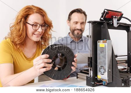 Professional 3d designer. Delighted positive nice woman having a filament coil in her hands and smiling while enjoying her work with 3d technology