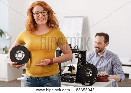 Important detail. Happy delighted smiling woman holding 3d filament and pointing at it while showing it to you