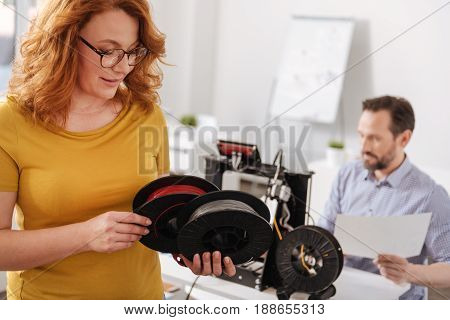 Modern 3d design. Pleasant beautiful smart woman holding two coils of filament and choosing one of them while working with 3d printing technology