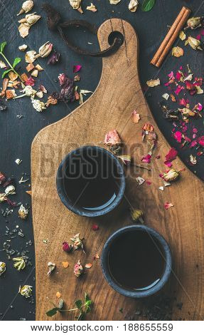 Chinese black tea in black stoneware cups on serving wooden board over black wooden background with herbs, flower buds, tea leaves spilt around, top view, vertical composition