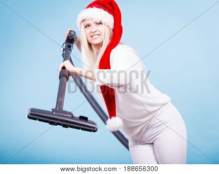 Woman vacuuming the house. Positive smiling teen girl in santa helper hat with vacuum cleaner. Christmas time and housework concept.