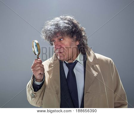 The senior man in cloak as detective or mafia boss with With a magnifying glass. Studio shot on gray in retro stile. Concept of Search