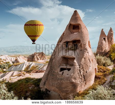 Rock formations and balloon in Pigeon Valley of Cappadocia , Turkey