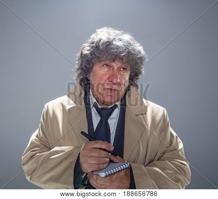 The senior man in cloak as detective or mafia boss writing in a notebook with pen. Studio shot on gray in retro stile