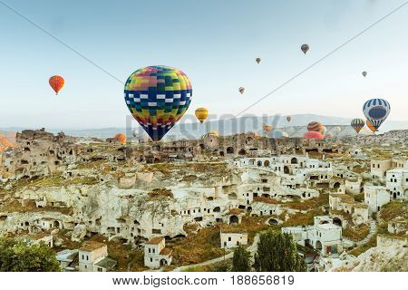 Colorful hot air balloons flying over Goreme town Cappadocia, Turkey. Old historic buildings in Goreme national park