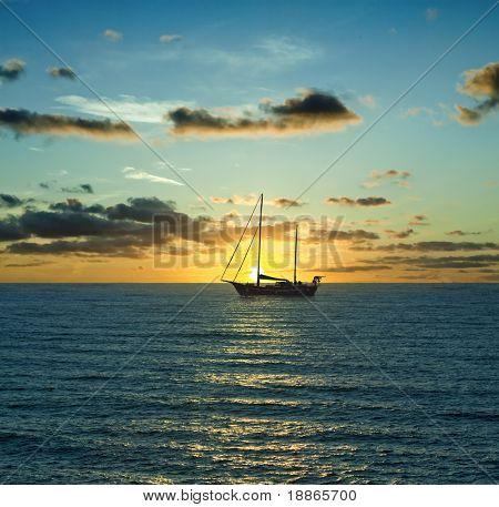 Barca a vela e il tramonto sul Mar Mediterraneo
