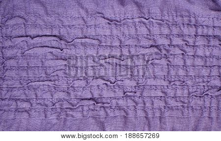 Closeup of purple fabric with irregular stitched folds for background