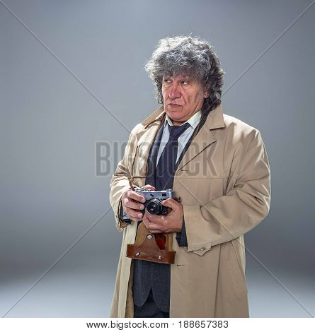 The senior man in cloak as detective or mafia boss with photo camera. Studio shot on gray in retro stile