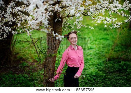 Young Beautiful Girl In A Pink Shirt Standing Under Blossoming Apple Tree And Enjoying A Sunny Day.