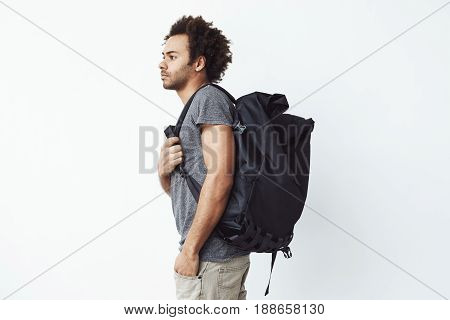 Handsome african man with rucksack standing in profile over white background. Copy space.