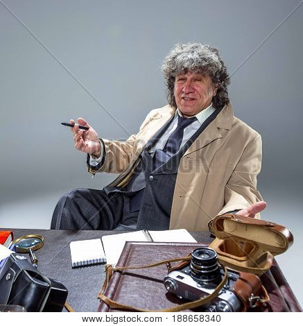 The senior man in cloak as detective or mafia boss writing in a notebook with pen at table. Studio shot on gray in retro stile