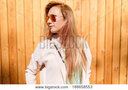 Photo of long-haired woman looking sideways in sunglasses against background of wooden wall