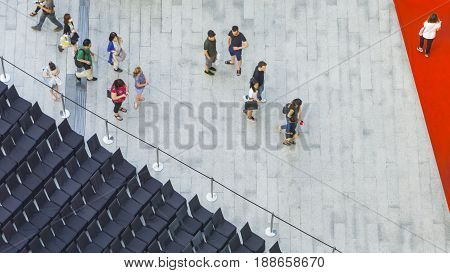 people walk on across the pedestrian concrete landscape in the city street with the red carpet and the zoning of black seat chairs (Aerial top view)