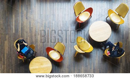 Aerial top view of business people sitting on chair with table desk with laptop and book in public space on the interior wood furniture and pattern wood floor.