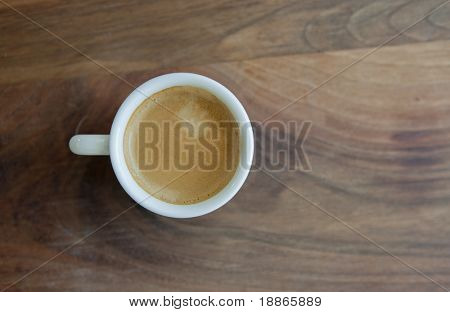 Espresso in a classic cup on a wooden table top view