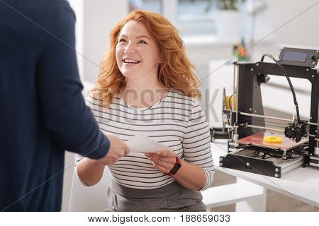 Friendly colleagues. Pleasant good looking cheerful woman sitting on the chair and taking a document while looking at her designer colleague