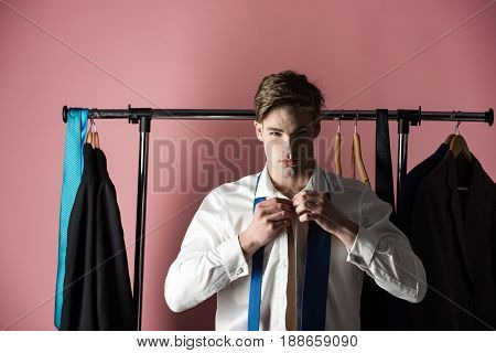 man with shaved face at wardrobe hanger with formal outfit tie and suit wearing shirt and tie on pink background