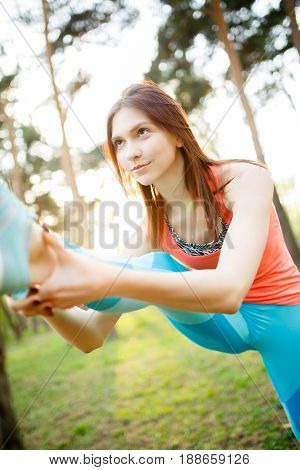 Young woman doing sports in morning spring forest. Lensflare effect