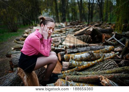 Beautiful Young Woman Sitting And Holding His Head With His Hands, On Stack Of Felled Tree Trunks In