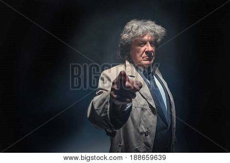 The senior man in cloak standing as detective or mafia boss and pointing at camera. Studio shot on gray in retro stile in the light and smoke ray
