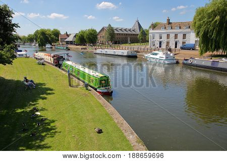 ELY, UK - MAY 26, 2017: The riverside in Spring with moored barges on the Great Ouse river and traditional houses