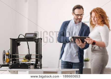Sophisticated technological device. Selective focus of a professional 3d printing machine standing in the table with delighted positive designers working in the background