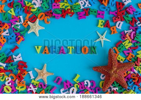 VACATION - word composed of small colored letters. Summer vacation souvenir - starfish from tropical sandy ocean beach, holidays abroad - summertime top view concept.