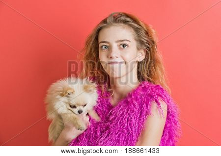 girl or cute woman with natural blond long wavy hair smiling with closed mouth on young face no makeup in pink feather boa and small spitz dog pet in hands on red wall. Fashion friendship