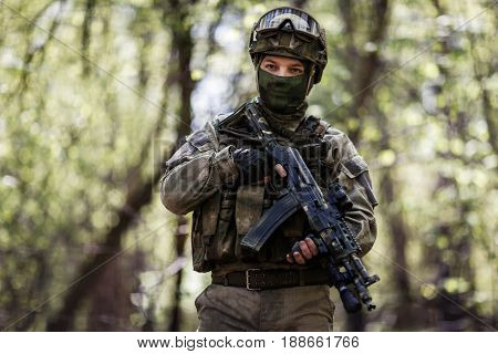 Soldier in helmet and mask patrols forest during day