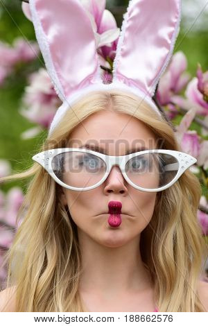 woman or cute girl with long blond hair making fish face lips grimace in funny glasses and rosy bunny ears on blossoming floral environment. Spring. Easter. Holidays celebration