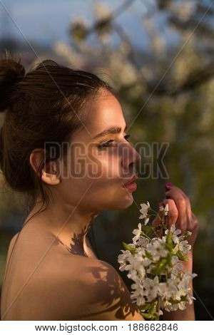 spring blossom woman or sexy girl with naked shoulders and hair bun with white blossoming flowers in garden on sunny spring day on blurred natural environment. Springtime youth and loneliness