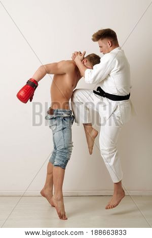 Sport And Combat, Karate Athlete Jumping, Kicking Knee At Boxer