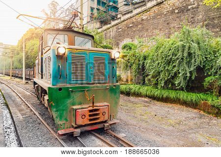Electric narrow-gauge locomotive stands with the freight train with coal before departure. Yuejin. Jiayang Mining Region. Sichuan province. China.