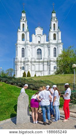 POLOTSK BELARUS - MAY 19 2017: Unknown young people are near cult complex (source and stone-altar). On background - St. Sophia Cathedral Polotsk Belarus