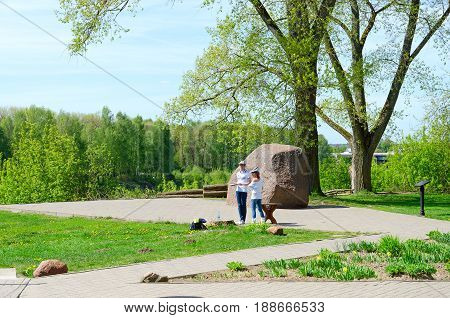 POLOTSK BELARUS - MAY 19 2017: Unknown young people at Borisov's stone with inscriptions of XII century. One of five Borisov stones which were in riverbed of Western Dvina preserved three of them