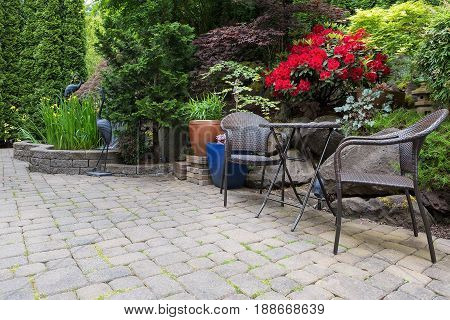Garden backyard with lush plants landscaping pond water fountain and stone paver patio hardscape with wicker bistro furniture chair and table set