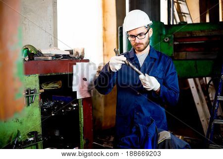 A portrait of a factory worker operating a lathe