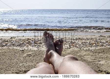 The Legs Of A Man On A Beach Background. A Man Lies On An Amatrace On The Beach And Is Resting. Legs