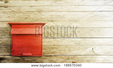 the red wood mailbox on the wood pattern background.