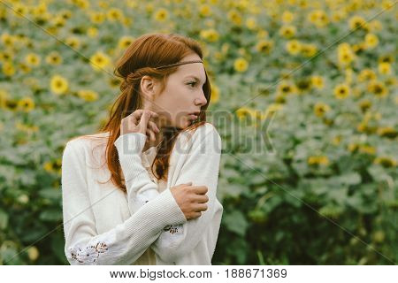 Profile of a beautiful girl against a background of sunflowers. Proper facial features.