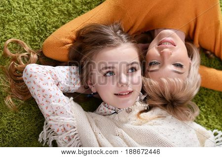 Mother and daughter lying on green carpet, top view
