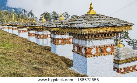 Dochula pass 108 chortens (Asian stupas) is the memorial in honour of the Bhutanese soldiers in the Timpu city with the grass landscape and cloudy sky background Bhutan