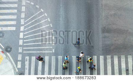 people walk to pedestrian crosswalk on traffric road (Aerial photo top view)