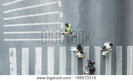 Busy city people are walking to pedestrian crossing on traffic road (Aerial photo top view)
