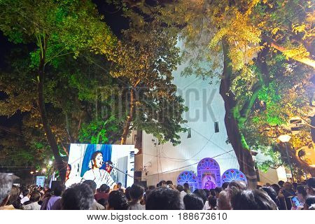 KOLKATA WEST BENGAL INDIA - 9TH MAY 2017 : Female singer performing and seen in a giant screen amongst audience at Rabindra Jayanti celebration (birthday of Late Nobel winner Poet Rabindranath Tagore).