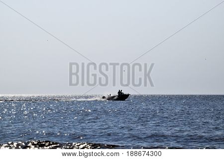 The boat rushes by the sea. In the boat people. Seascape in the evening. Silhouette of a motor boat and people in it against the background of the sea distance.