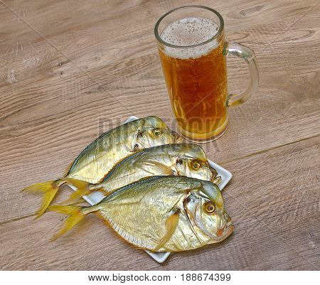 Dried fish and a glass of beer on a wooden table. Horizontal photo.